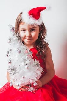La ragazza tiene nelle sue mani decorazioni fatte a mano - albero di natale da nastro d'argento