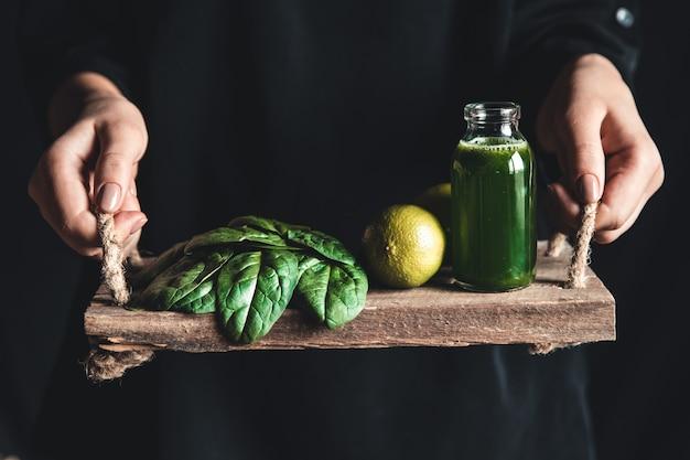 La ragazza tiene tra le mani un vassoio vintage con frullato di spinaci, lime e spinaci. cibo sano, eco, vegano.