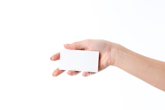 Una ragazza tiene nel suo primo piano di carta bianca con foglia di palma