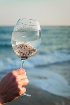 La ragazza tiene un grande bicchiere di vino con conchiglie su uno sfondo di mare blu