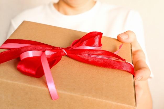 La ragazza porge un regalo avvolto in carta kraft con un fiocco di congratulazioni e consegna una scatola festiva
