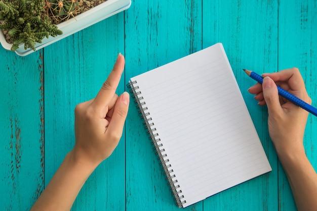 La ragazza tiene la matita, si prepara a scrivere in taccuino, tavolo in legno blu.