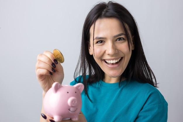 La ragazza tiene in mano un salvadanaio rosa e una moneta. il concetto di ricchezza e accumulazione.