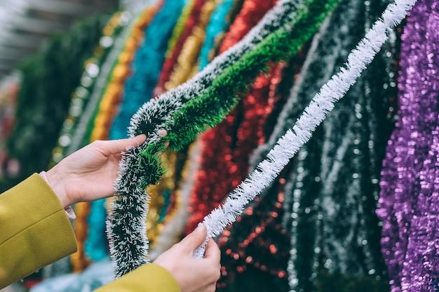 La ragazza tiene la pioggia nelle sue mani. decorazioni di natale capodanno sull'albero.