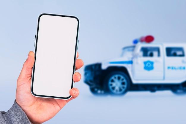 La ragazza tiene in mano uno smartphone. mock up telefono con schermo bianco sullo sfondo di un'auto della polizia.