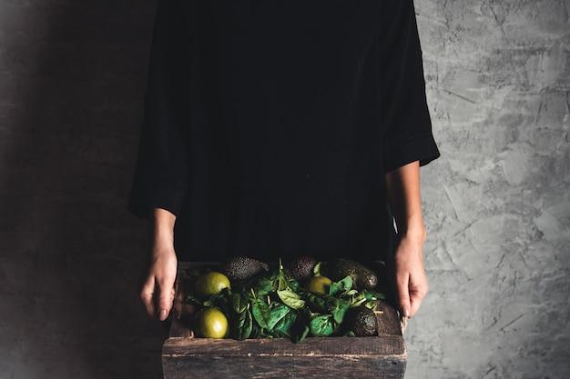 La ragazza tiene un frullato con spinaci, avocado e lime in una scatola vintage. cibo sano, vegano, eco.