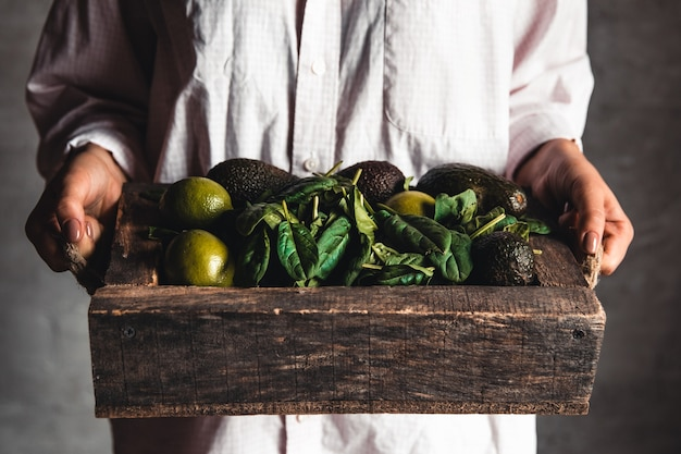 La ragazza tiene un frullato con spinaci, avocado e lime in una scatola vintage