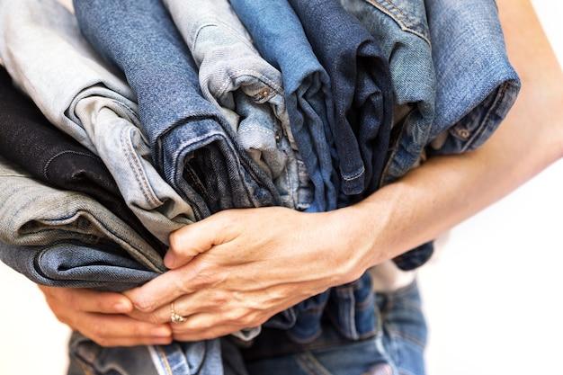 La ragazza tiene in mano una pila di jeans. pulizia nell'armadio.