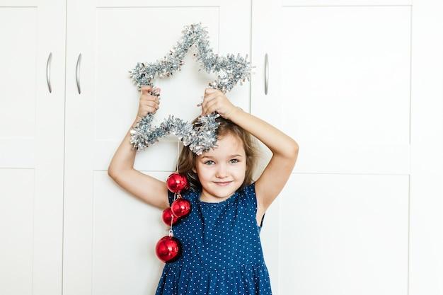 Una ragazza tiene una stella tra le mani per decorare la casa per il nuovo anno e natale, il bambino si prepara per le vacanze, aiuta i genitori, aspetta i regali
