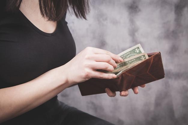 La ragazza tiene il portafoglio nelle sue mani e prende i soldi