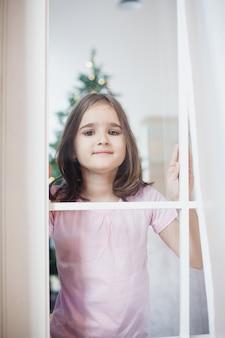 Ragazza a casa a natale dietro la finestra