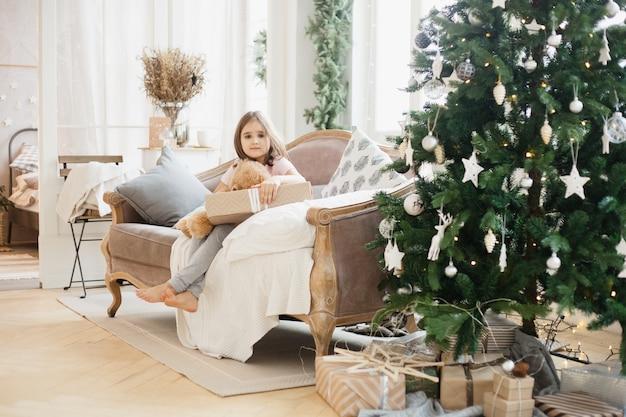 Ragazza a casa durante il natale con albero e regali