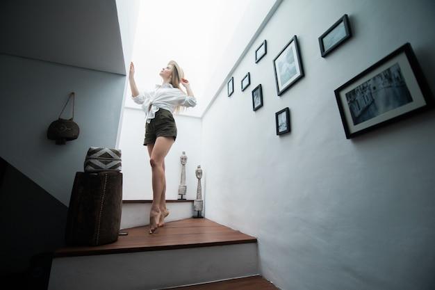 Ragazza a casa utilizzando l'app del telefono seduta sulle scale - giovane donna al chiuso utilizzando la tecnologia per chattare con le persone