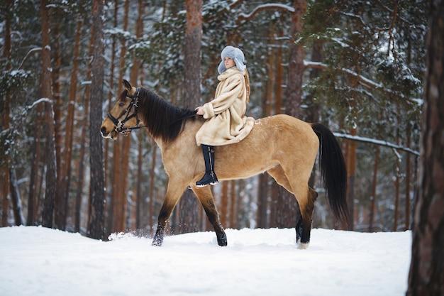 Ragazza a cavallo cammina in inverno attraverso un bosco innevato