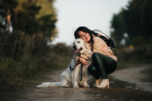 Ragazza che abbraccia un cane golden retriever nella foresta