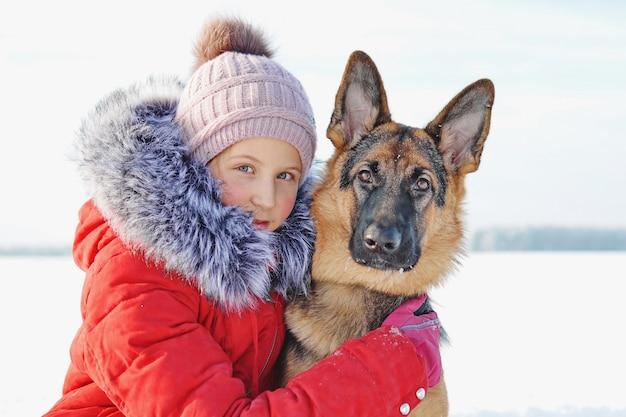 La ragazza che abbraccia il suo amato cucciolo nel parco innevato. cane da pastore tedesco e bambino sul bianco della neve nella giornata invernale. cura degli animali. stile di vita.