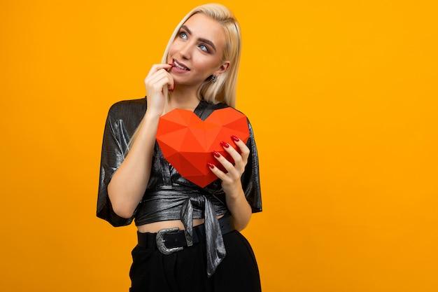 Ragazza abbraccia una figura di cuore 3d su uno sfondo di studio arancione