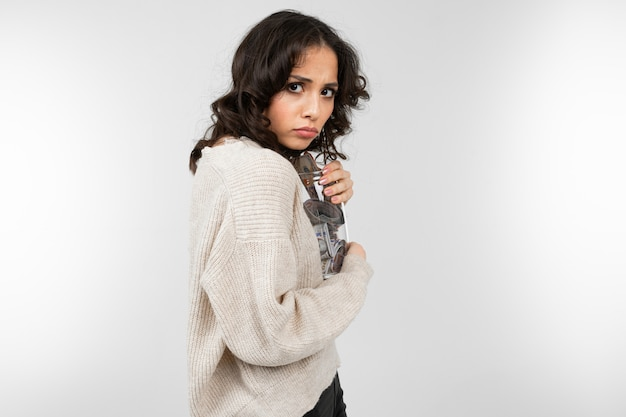 La ragazza abbraccia strettamente il suo salvadanaio in modo che non sia portato via su uno sfondo grigio