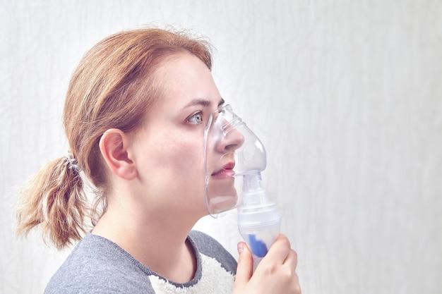 La ragazza inala la medicina attraverso il dispositivo per inalazione nebulizza, aiuta a fermare l'attacco d'asma.