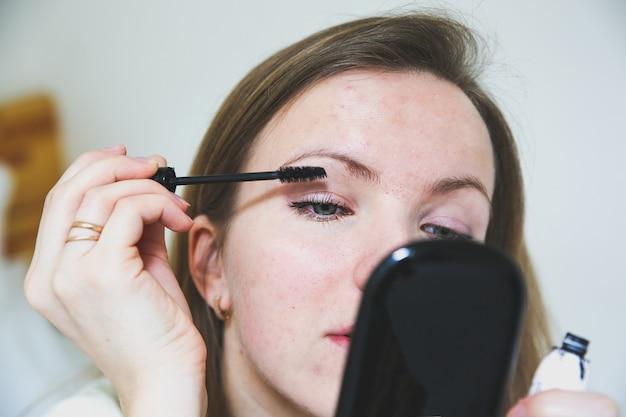 La ragazza sta applicando il trucco. mascara nero sulle ciglia. concetto di foto di bellezza.