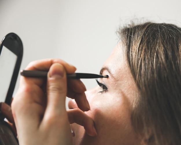 La ragazza sta applicando il trucco. polvere per sopracciglia con pennello. concetto di foto di bellezza.