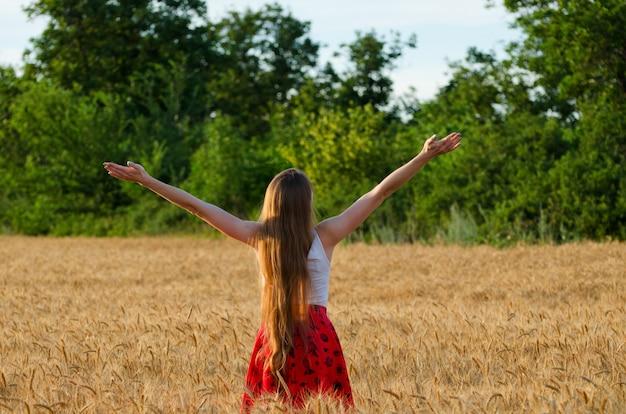La ragazza è tornata in un campo di grano con le braccia alzate al cielo