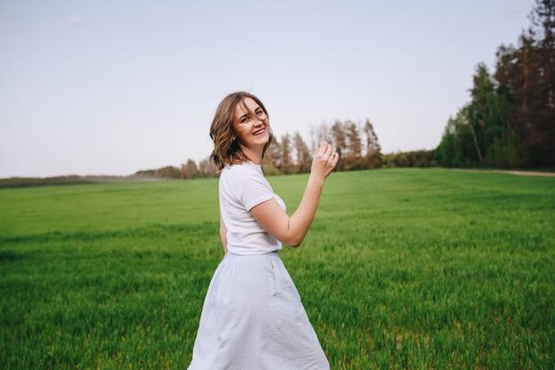 La ragazza è bionda, capelli castani, con una camicia bianca e una gonna longuette blu. camminando nel campo, attraverso l'erba verde. ritratto di una ragazza positivo e sorriso.