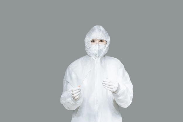 Una ragazza è un medico che tiene un tampone di cotone buccale e una provetta pronta a raccogliere il dna dalle cellule all'interno del paziente.