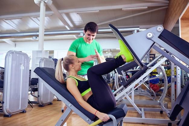 Una ragazza sta facendo esercizi sul simulatore di piede con personal trainer