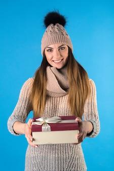 La ragazza è vestita con un caldo maglione lavorato a maglia e un cappello con una confezione regalo.