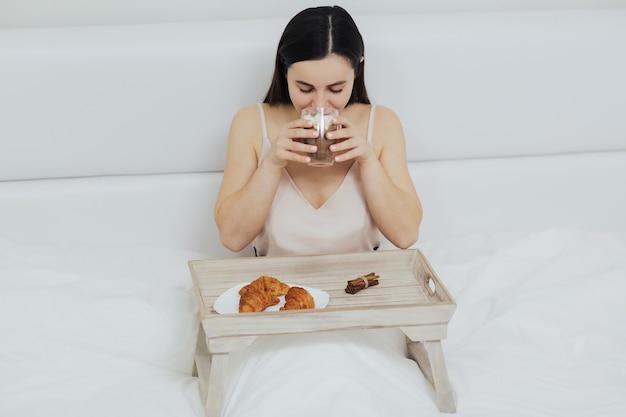 Ragazza sta bevendo una tazza di cappuccino con marshmallow e mangia croissant freschi
