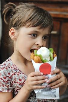 La ragazza sta mangiando un gelato con frutta e bolle di cialda all'aperto.
