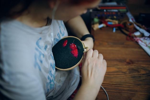 La ragazza sta ricamando un cappello a fungo su un panno verde fatto a mano, hobby, donna, filo interdentale per cucire con filo...
