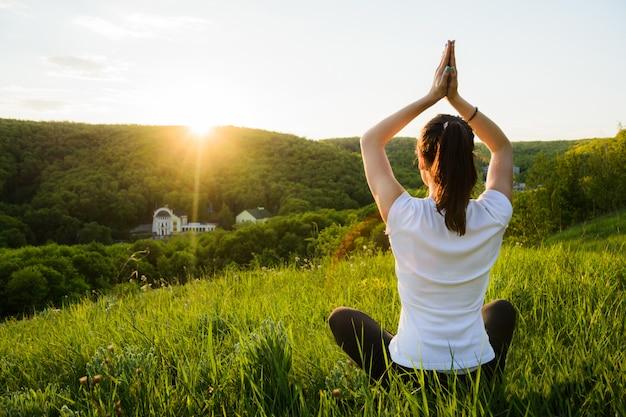 La ragazza è impegnata nella meditazione sulla natura Foto Premium
