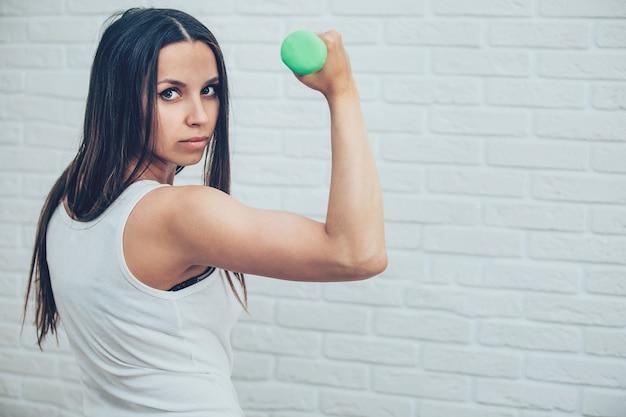 La ragazza è impegnata con i manubri a casa fitness