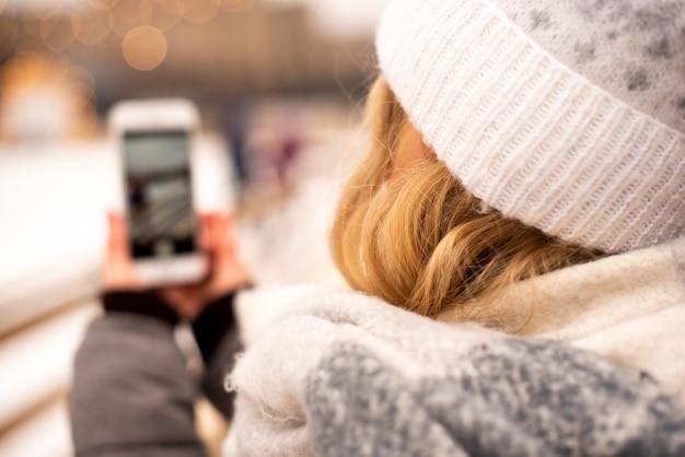 La ragazza sta girando il suo video blog alla fiera di capodanno. sullo sfondo vediamo una pista di pattinaggio