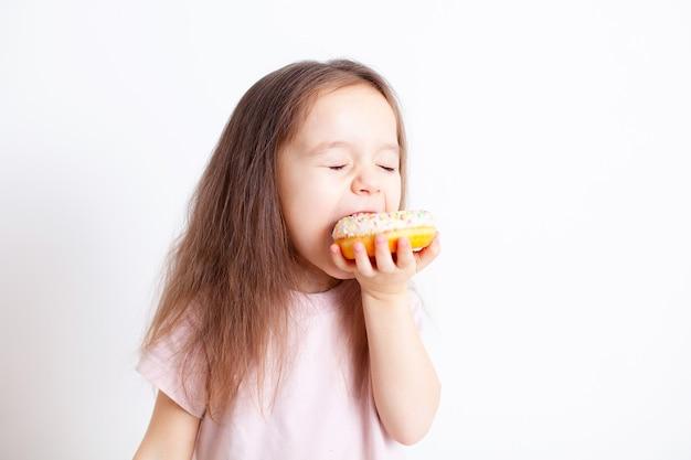 La ragazza è felice di addentare la ciambella fast food dolci snack cibo sano cibo dannoso