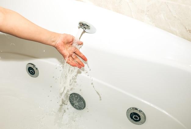 La ragazza tiene la mano sotto il flusso d'acqua nella vasca idromassaggio. bagno bianco per il relax. spruzzi d'acqua nel centro termale.