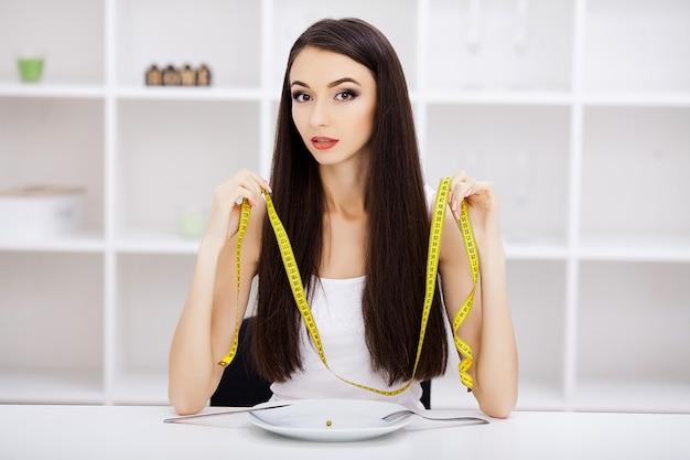 La ragazza sta tenendo un piatto e sta cercando di mettere un pisello sulla forchetta