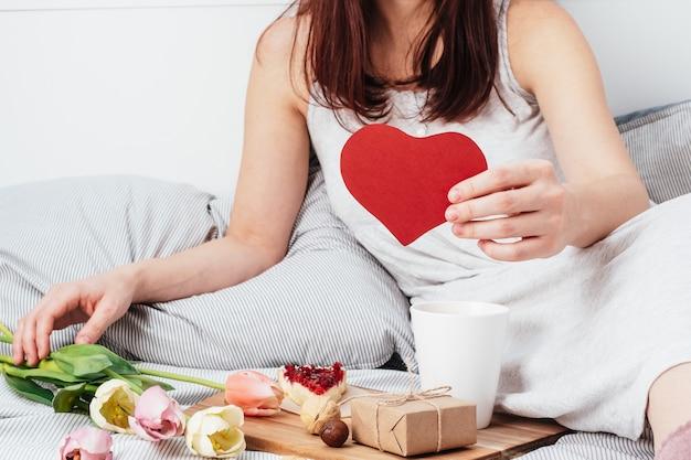 La ragazza tiene in mano un cuore rosso. congratulazioni per san valentino il 14 febbraio. colazione a letto e regalo.