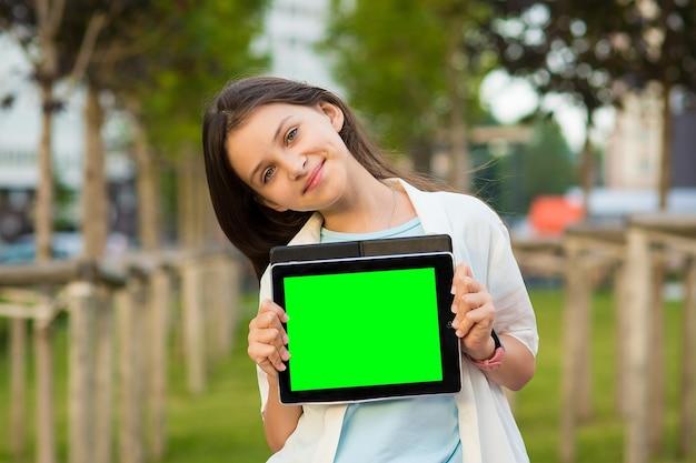 Una ragazza tiene in mano uno schermo vuoto del tablet all'aperto