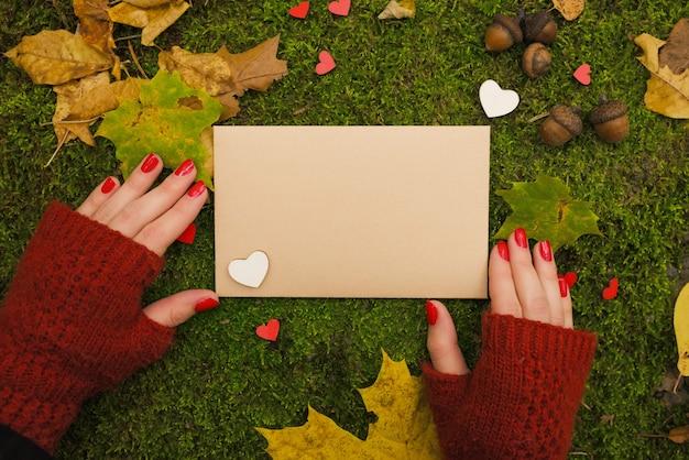 La ragazza sta tenendo un foglio di carta vuoto vintage nel parco d'autunno.