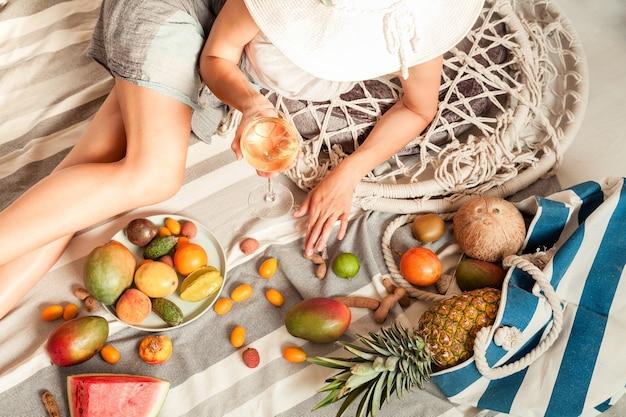 La ragazza è sdraiata su un picnic estivo con vino e frutta