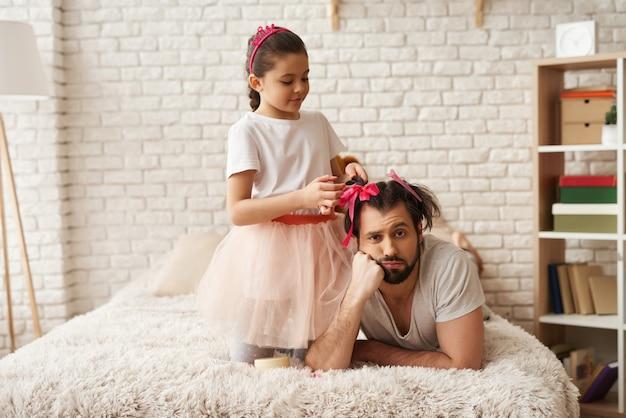 La ragazza sta facendo l'acconciatura di nuovi papà. festa della famiglia caucasica