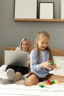 La ragazza sta giocando mentre la mamma guarda lo schermo del laptop. funziona o effettua acquisti online.