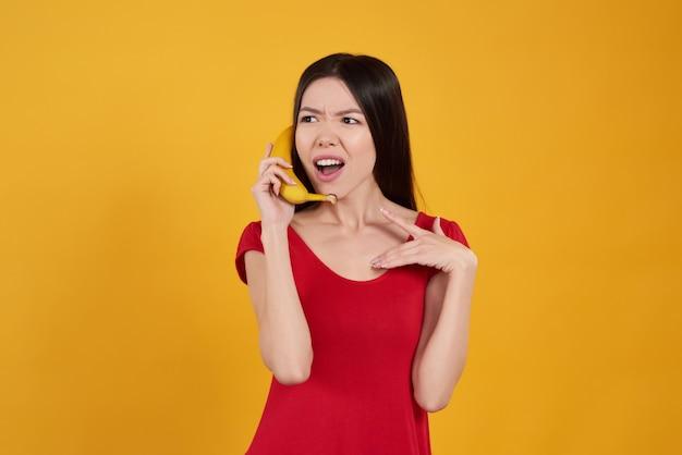 La ragazza sta proponendo con la banana su giallo.