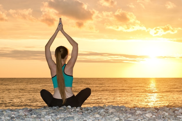 La ragazza sta praticando lo yoga sulla spiaggia. vista dal retro, tramonto