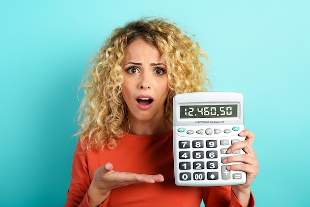 La ragazza è scioccata e mostra il suo debito sul display della calcolatrice. sfondo ciano