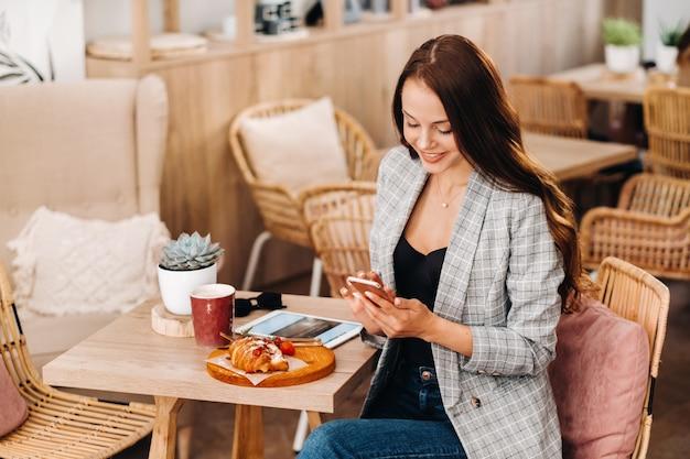 Una ragazza è seduta in un bar e guarda il suo smartphone, una ragazza in un bar sorride e scrive sul suo smartphone, i dolci sono sdraiati sul tavolo.