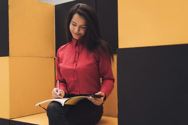 La ragazza è seduta in mobili moderni. lei è nel negozio.